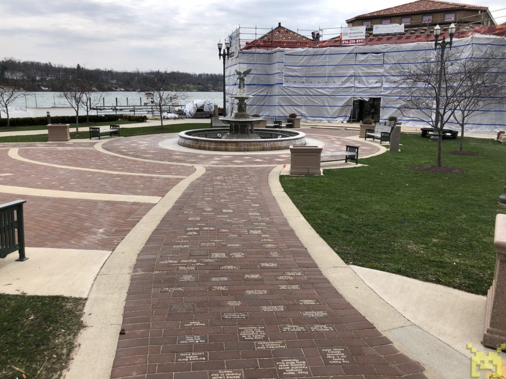 A brick walkway leading to a fountain