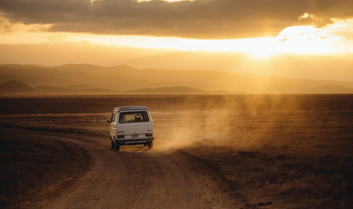 Volkswagon driving down road into sunset