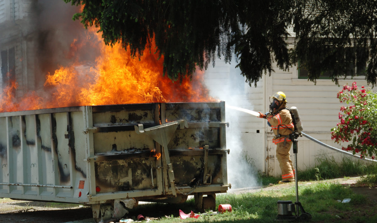 Firefighter putting out fire in dumpster