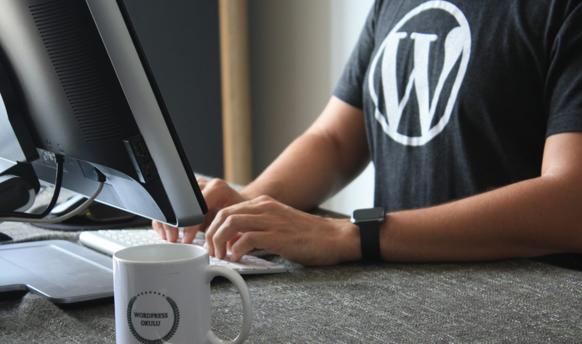 Man wearing WordPress logo shirt sitting at desktop computer