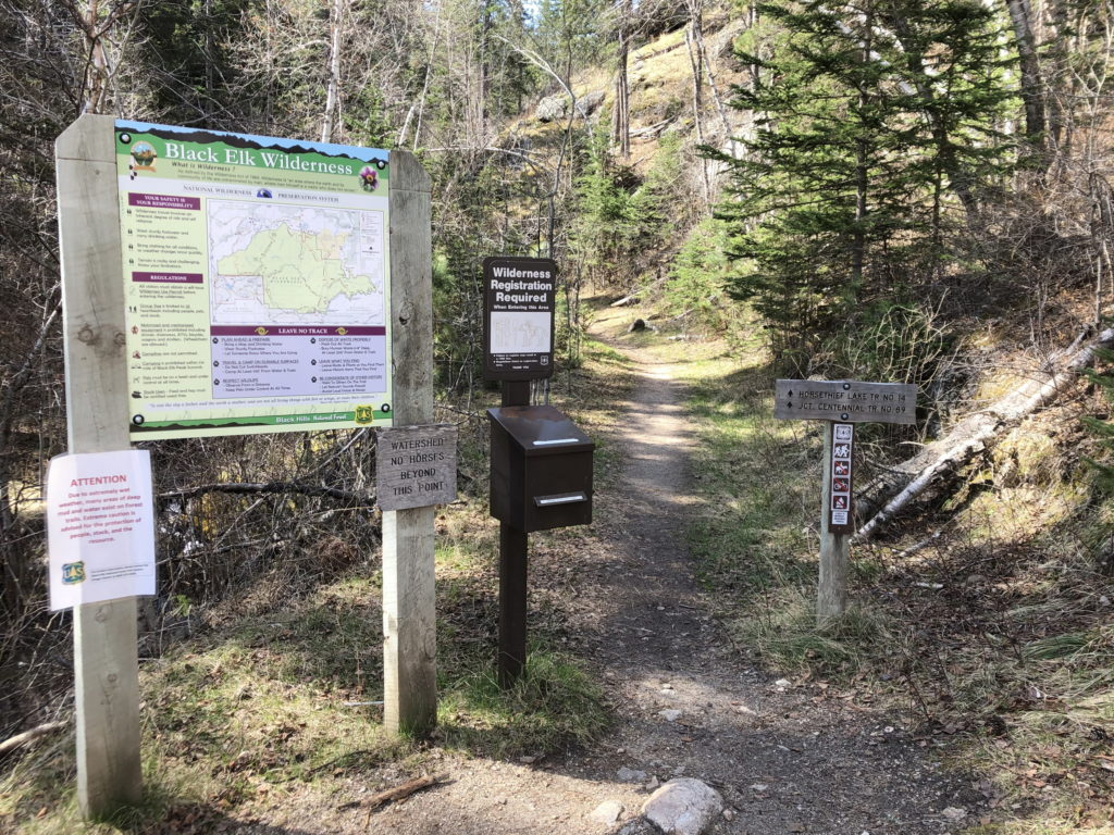 A trailhead with many signs and maps