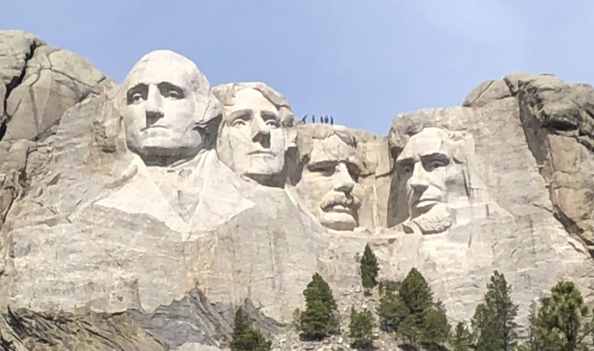 Mount Rushmore with people standing on Theodore Roosevelt's head