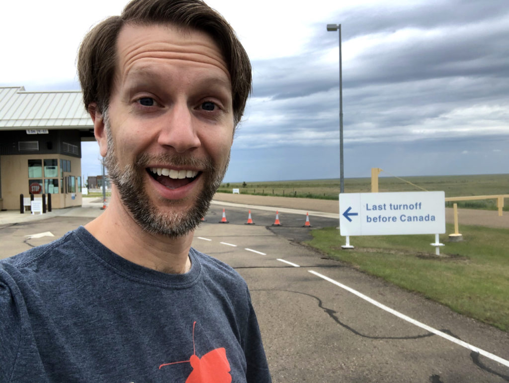 "Ken in front of sign: ""Last turnoff before Canada"""