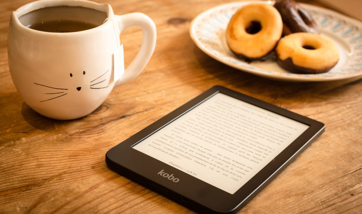 Kobo ereader on table with coffee and donuts