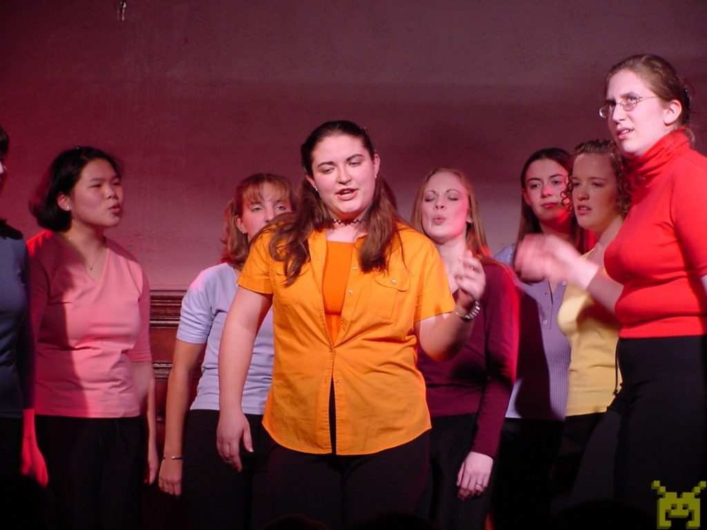 A women's a cappella group performs on stage