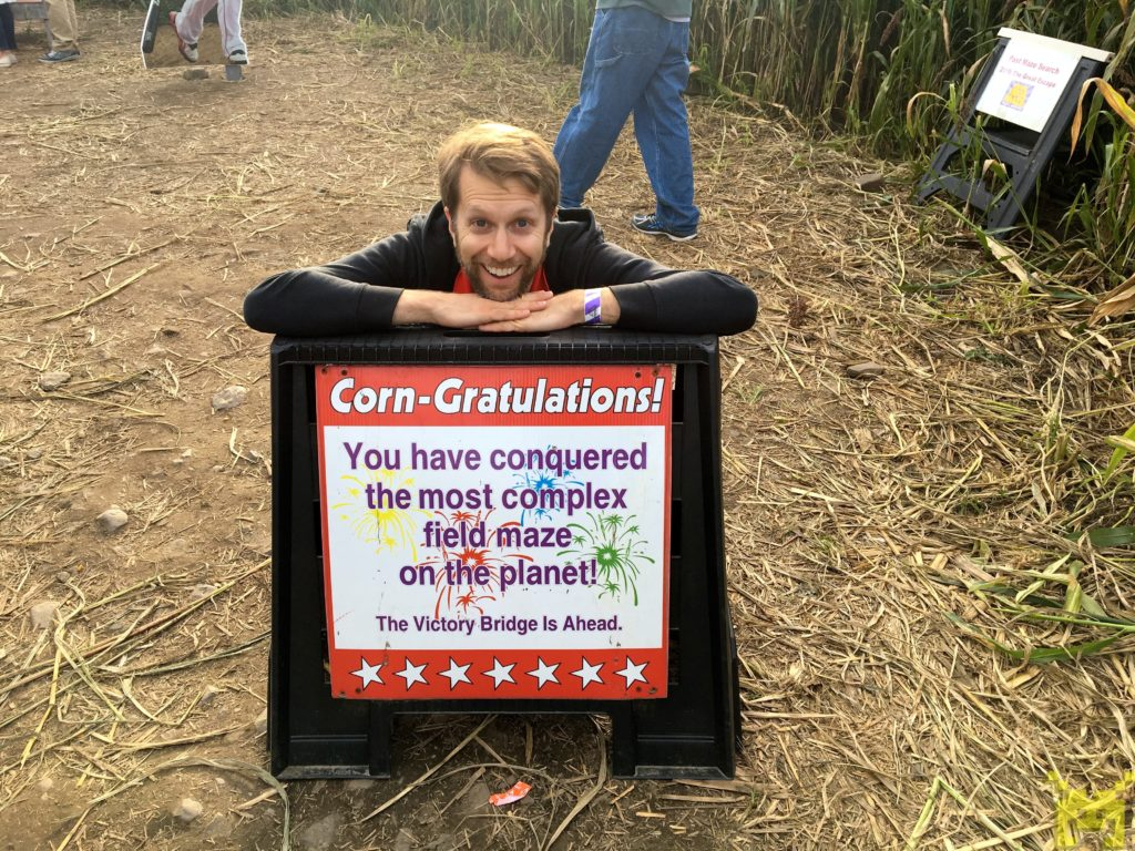 Ken in front of a sign declaring the end of the maze