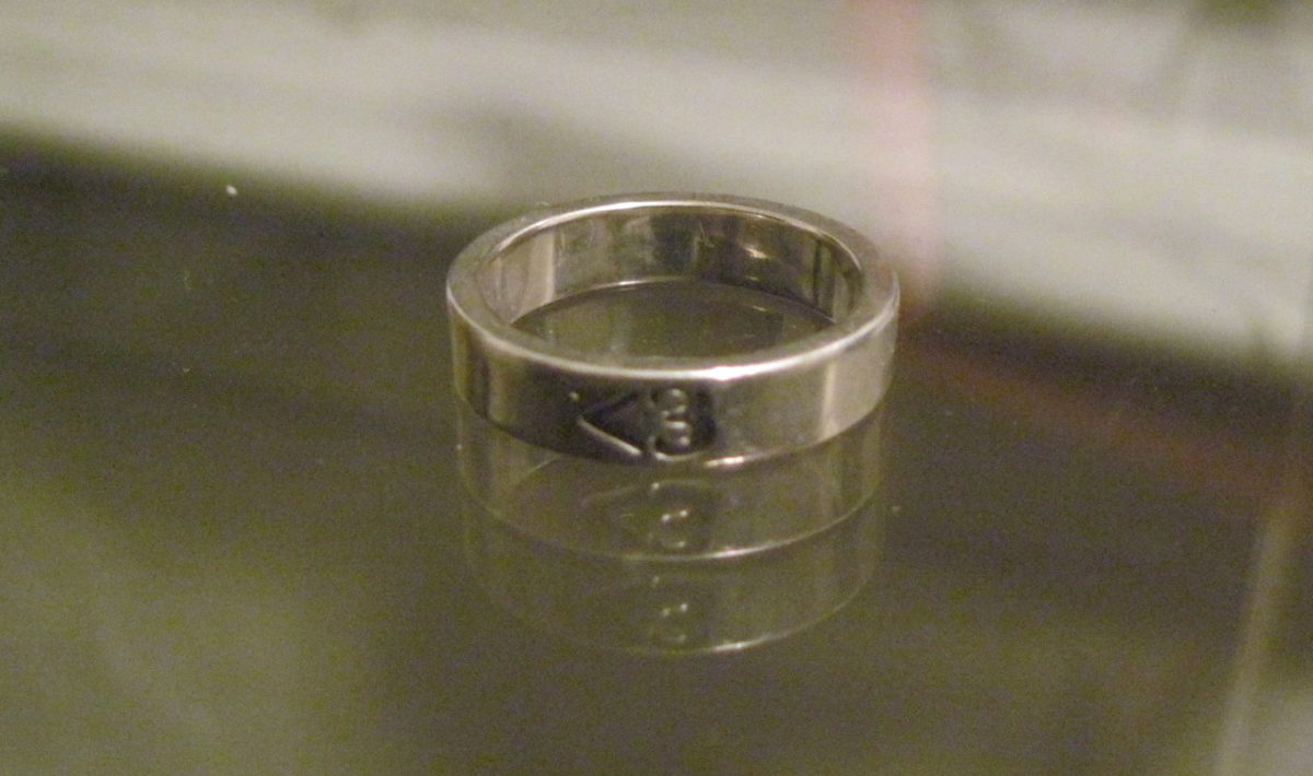 A silver ring with the symbols less than three