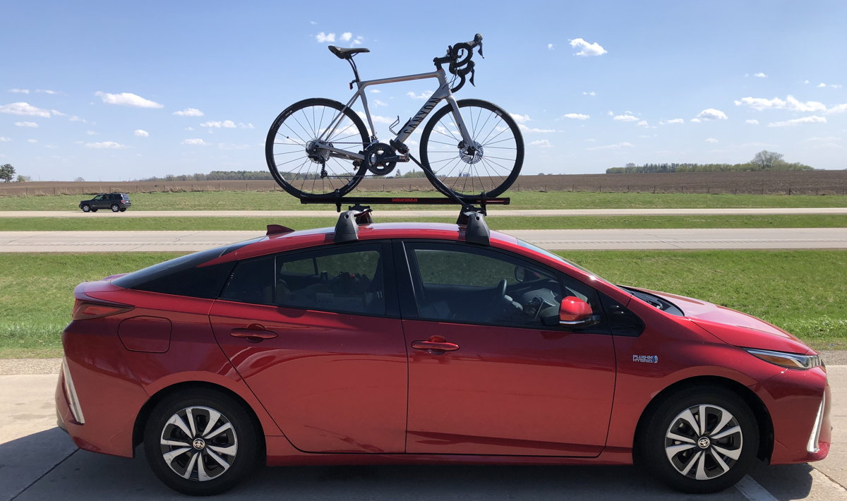 A profile shot of a Toyota Prius Prime 2017 with bike mounted atop car