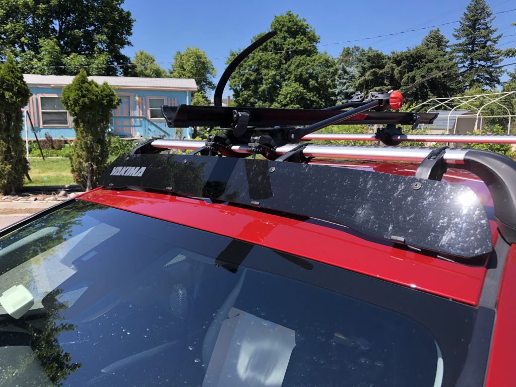 A wide black plastic board stretching from a car's roof top to the roof rack