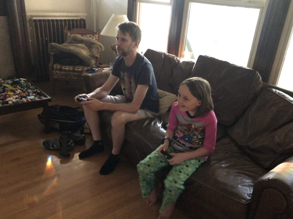 Ken on a couch playing Nintendo with a young girl