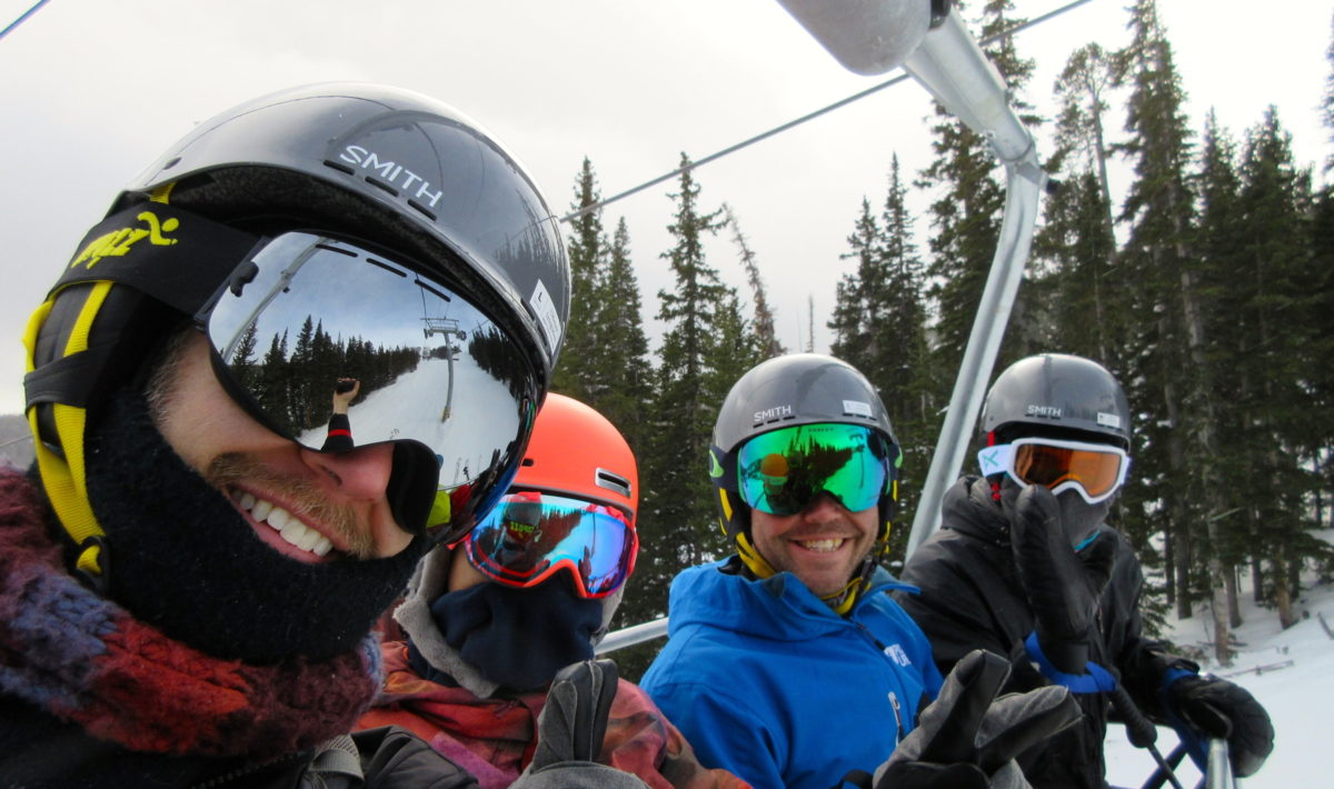 Four helmeted skiers on a chairlift