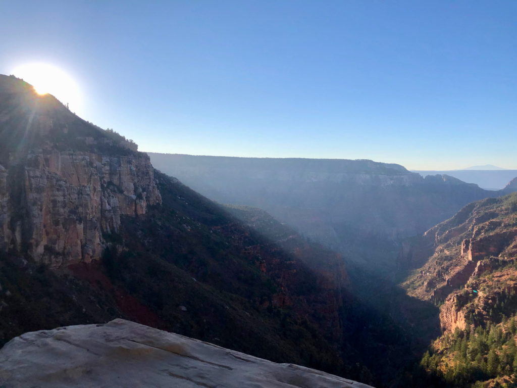 A sun casts shadows down into the canyon