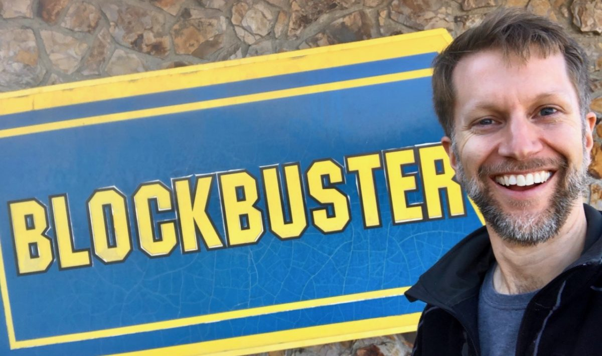Ken standing in front of a worn Blockbuster Video sign on building
