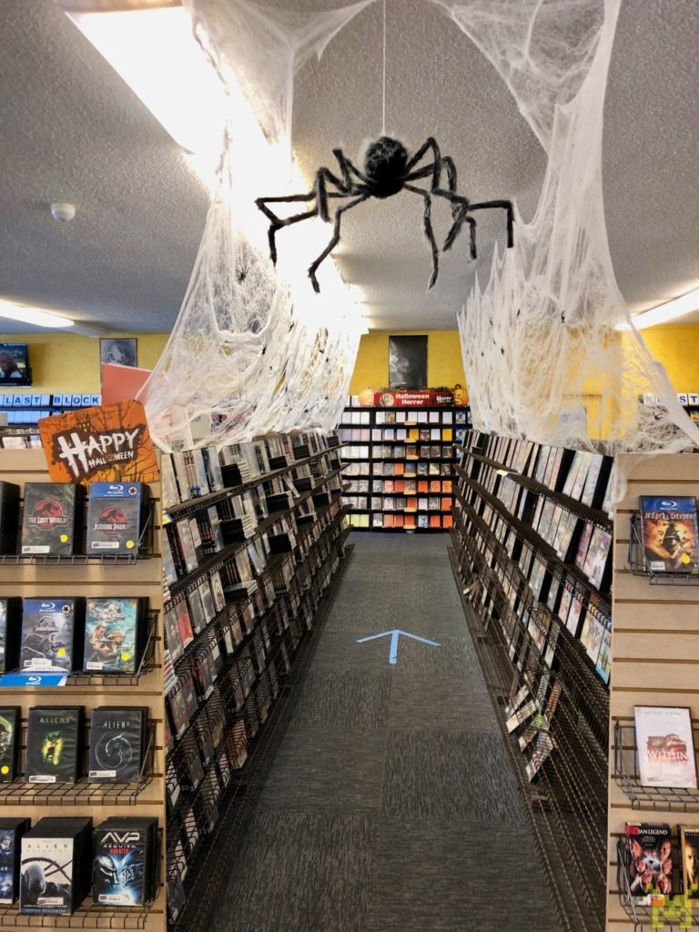 A row of movies with fake cobwebs and a spider hanging over it