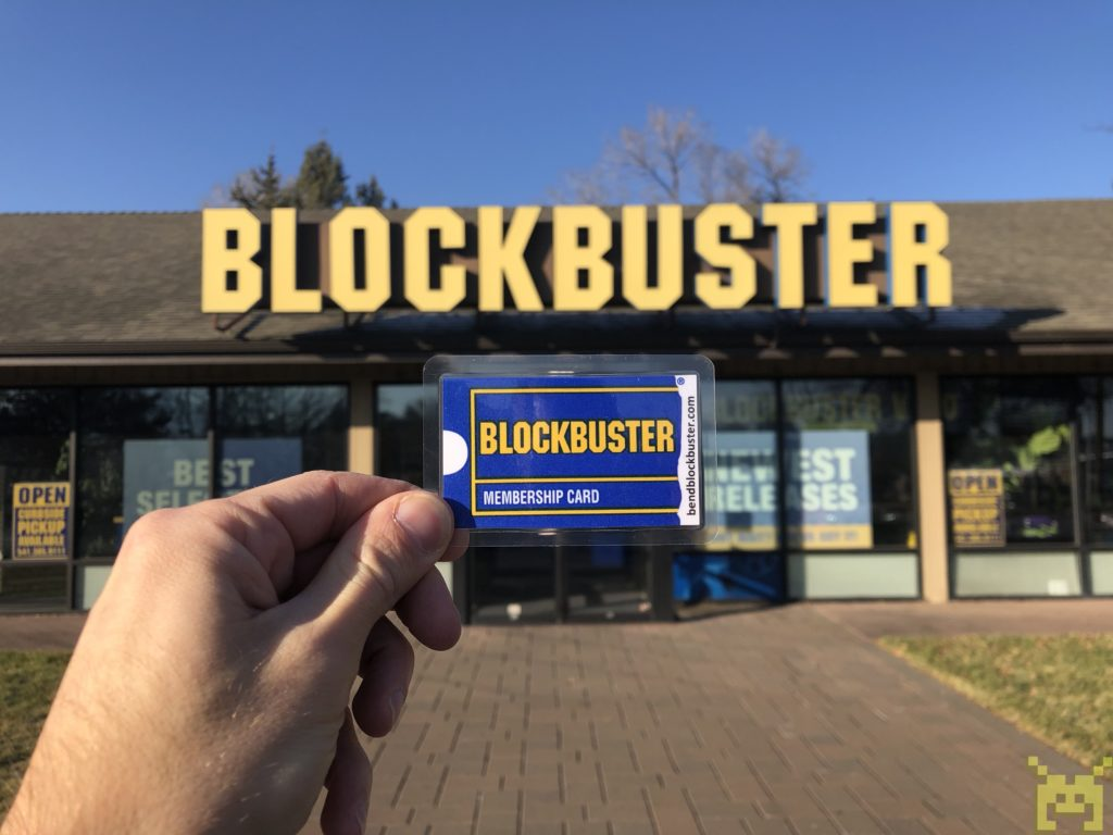 Ken holding a Blockbuster Video membership card in front of the store