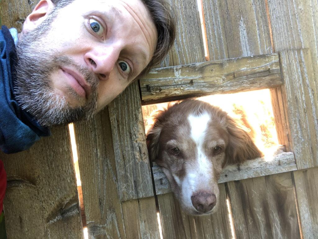 Ken poses for a selfie with a brown dog sticking its nose out a rectangular hole in a wooden fence