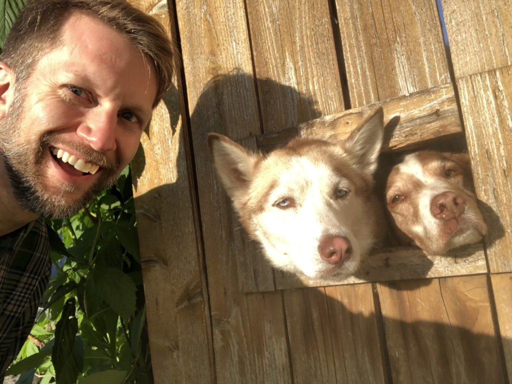 Ken poses for a selfie with two dogs sticking their heads out a rectangular hole in a wooden fence