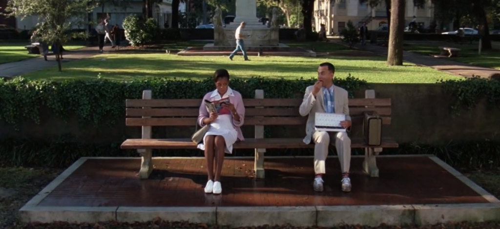 Tom Hanks as Forrest Gump sitting on a bench
