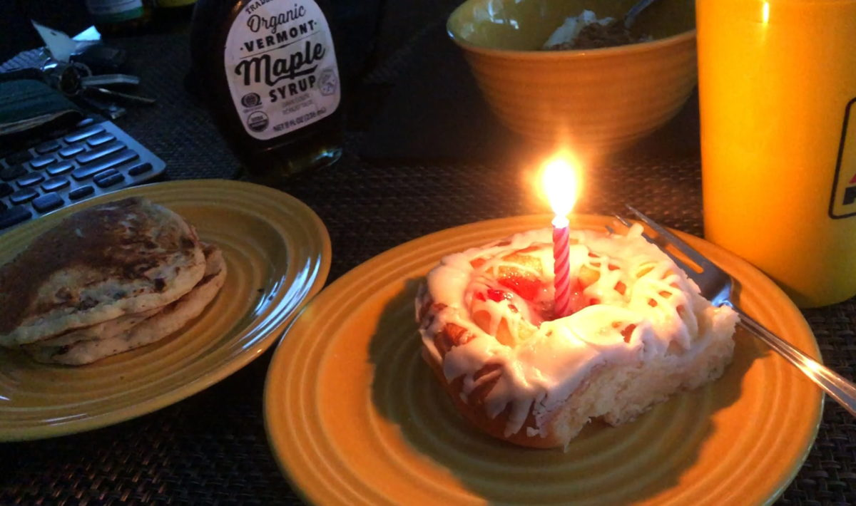 A danish pastry with a single lit candle