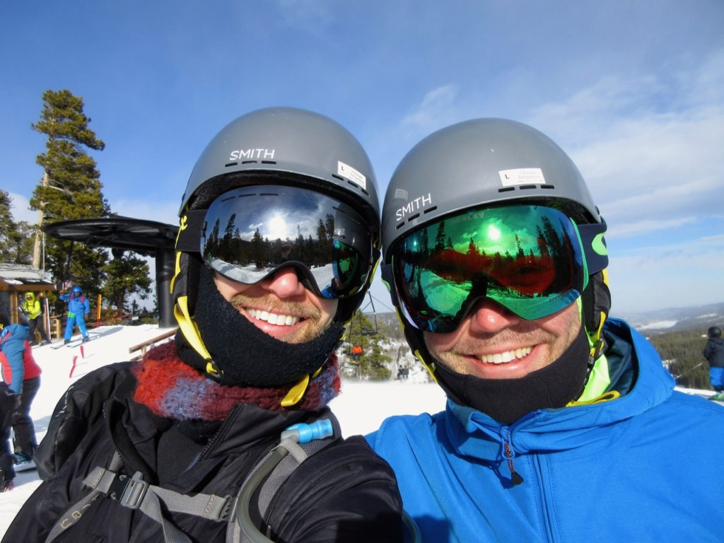 A selfie of Ken and Jack atop a sunny ski mountain