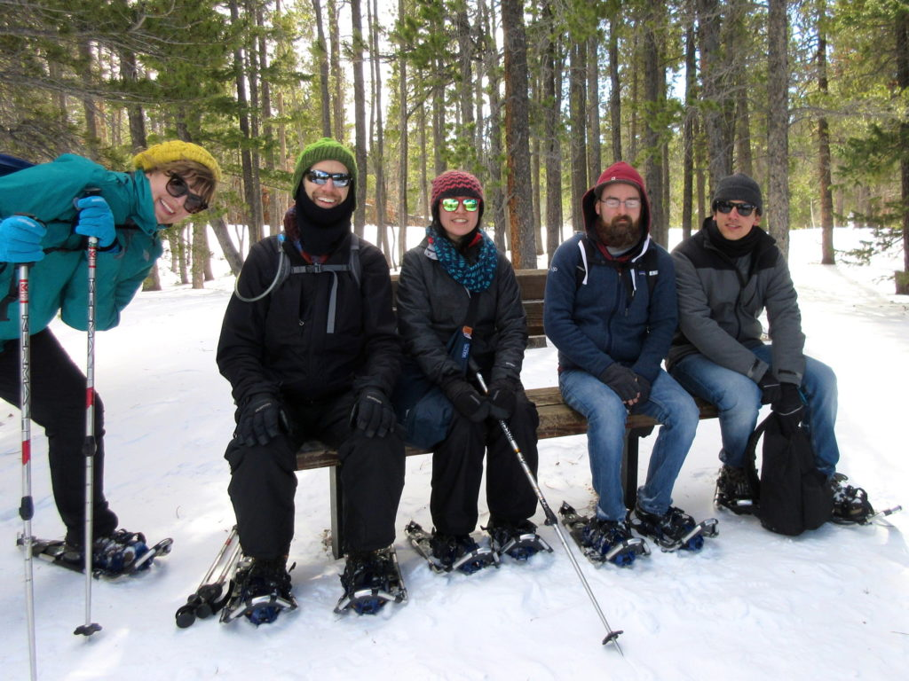 Ken and co-workers rest on a bench while snowshoeing