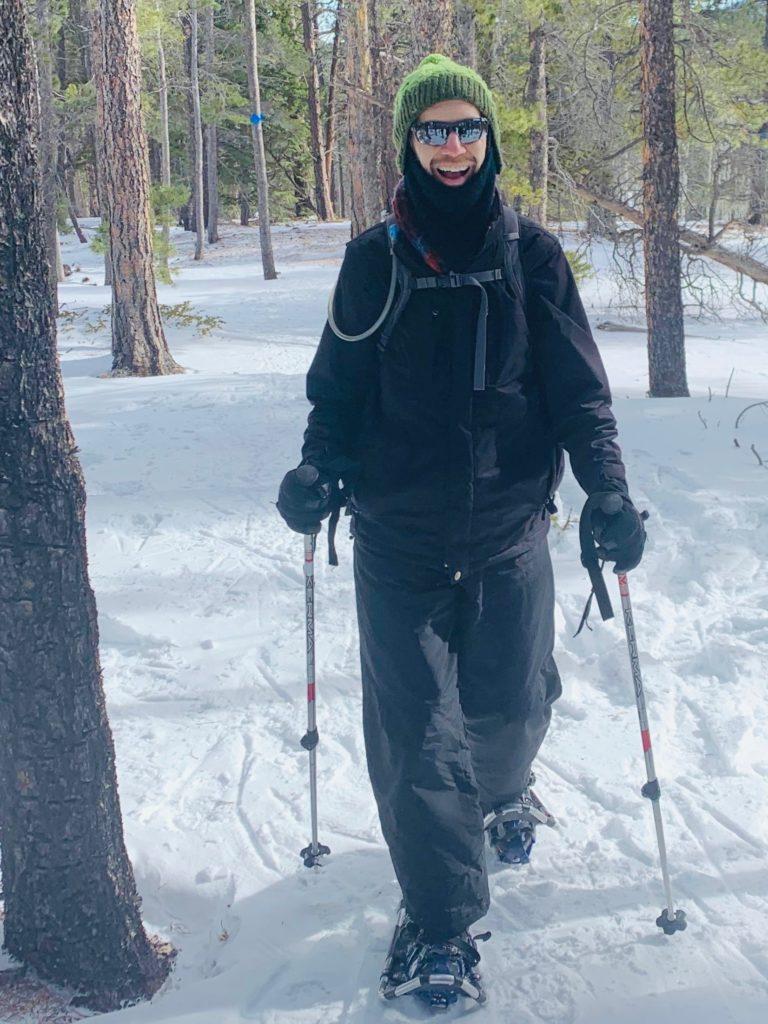 Ken grins while snowshoeing toward the camera