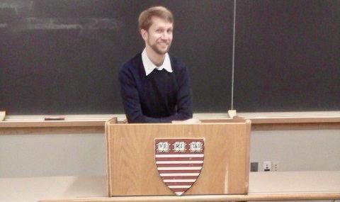 Ken standing in a classroom behind a Harvard-branded lectern