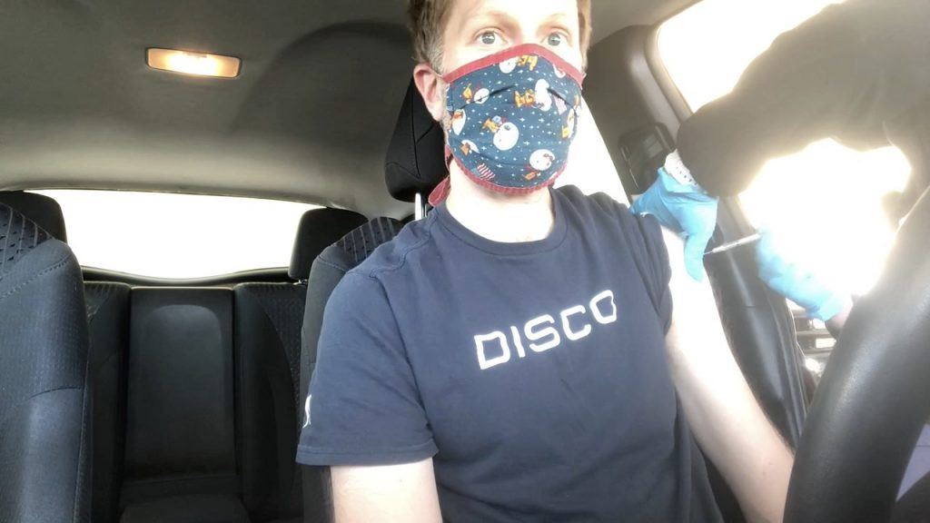 Dashboard view of Ken getting vaccinated while sitting in his car