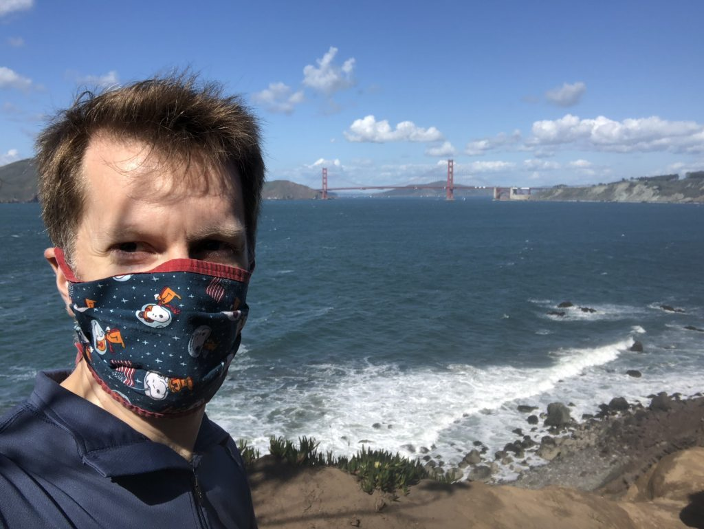 Selfie of Ken wearing a mask with the ocean behind him; in the distance is the iconic Golden Gate Bridge