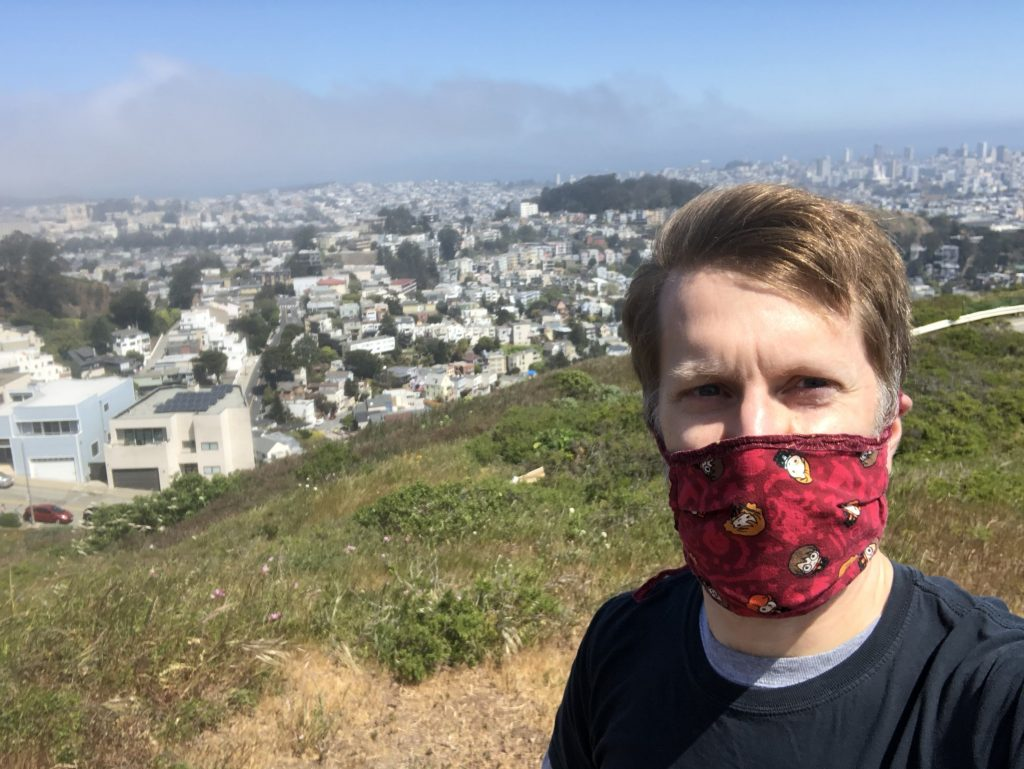 Selfie of Ken wearing a mask on a hill with the Outer Sunset neighborhood behind him