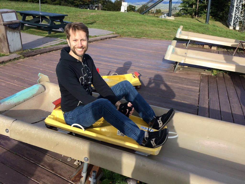 A smiling man sitting on a snow sled resting on a fiberglass chute