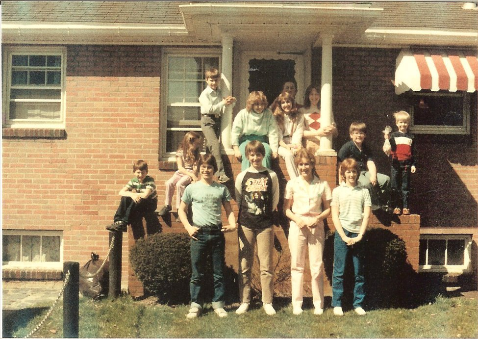 A family photo of a dozen kids on the front steps into a brick house